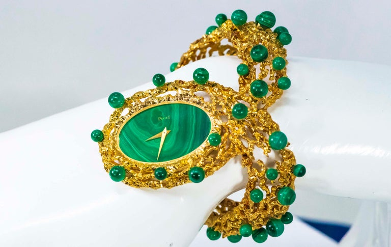 An Extremely Rare & Impressive Vintage 1970s Piaget w/ 18kt Yellow gold Textured Openwork bangle Design & highly sought after Malachite Dial and Malachite Rondel Motif Pattern Running Along the Bangle Cuff Bracelet   Timepiece Dimensions:  - 32mm X