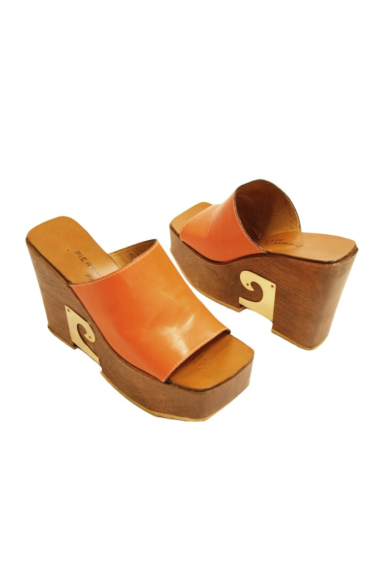 Amazing wooden clog sole shoes by Pierre Cardin. These tall platform heels feature a deep orange mule top strap and a leather sole. The thick wooden platform heels are contrasted sharply the iconic Pierre Cardin swirl logo on the outer side of the