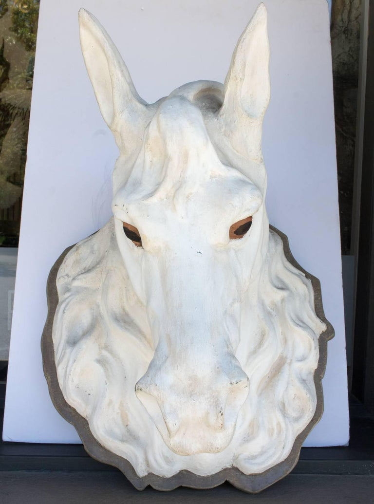This 19th century trade sign in the shape of a horse head is handcrafted in zinc and painted white and once hung in a Parisian atelier. The eyes are a wonderful amber color and this piece is mounted onto a wood plaque. Uncovered in Paris, France,