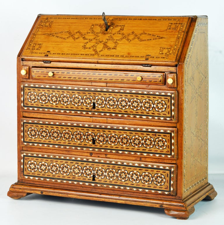This rare and charming miniature slant front chest is created in the Georgian style with elaborate bone and veneer inlay as well as certain details in the oriental style. The chest features an inlaid slanted front opening up to an interior fitted