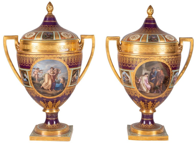 A rare and impressive garniture of three late 19th century Vienna style porcelain lidded vases, each with a burgundy ground with gilded boarders, motif and foliate decoration, inset hand painted panels depicting classical