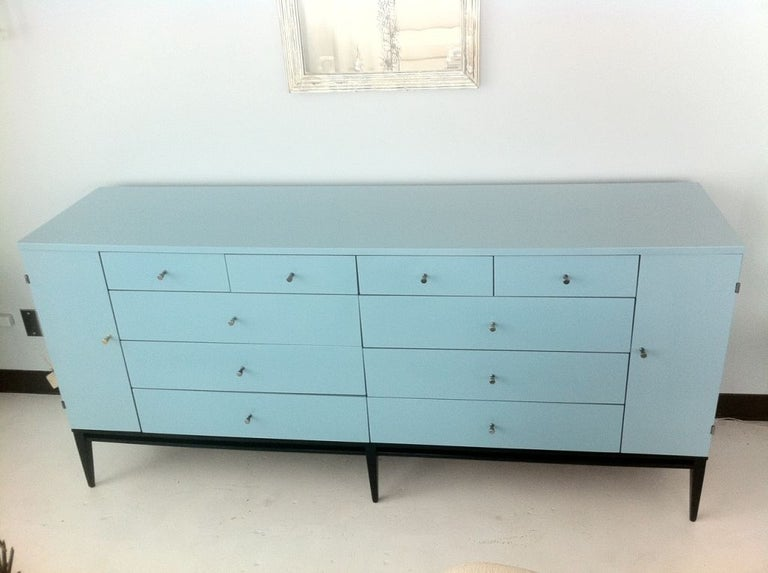 A lacquered commode / dresser by Paul McCobb shown with ebonized base, 10 drawers with nickel pulls flanked by two cabinet doors that each conceal 5 drawers. Lacquer color is Benjamin Moore peacock feathers. Current dresser shown is sold, will be