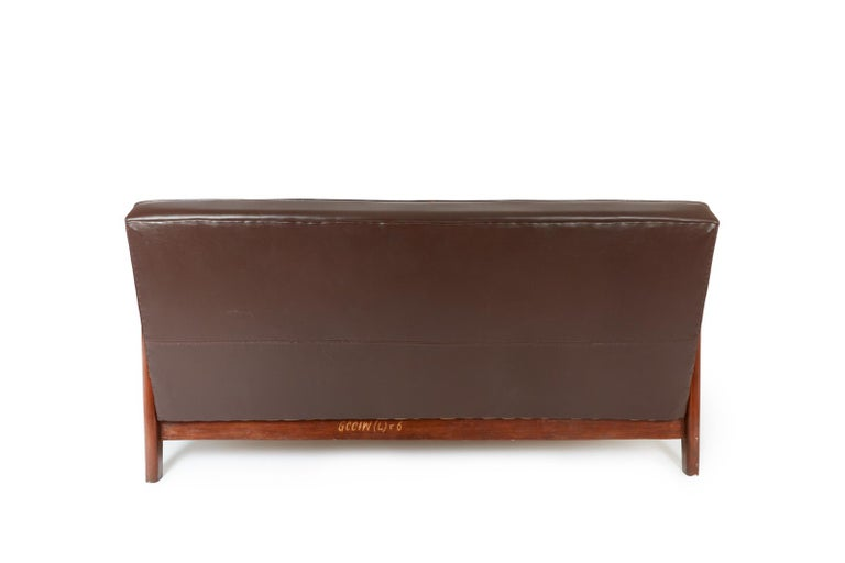 Rare sofa in teak and faux dark brown leather from the High Court of Chandigarh (Sector 1, Capitol Complex) designed by Pierre Jeanneret and Le Corbusier.  This model has a slightly sloping backrest and a solid bridge structure.  According to expert