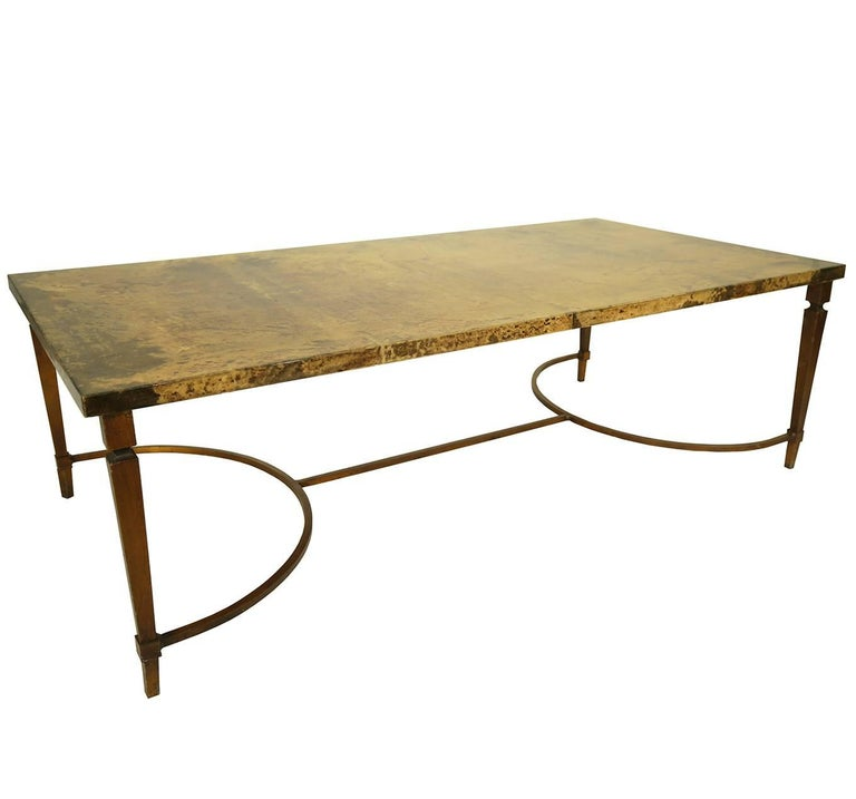 This rare 1960 Aldo Tura coffee table is an elegant statement piece. The lacquered goatskin top is a mottled golden hue, resting on brass coated forged metal legs and stretcher.