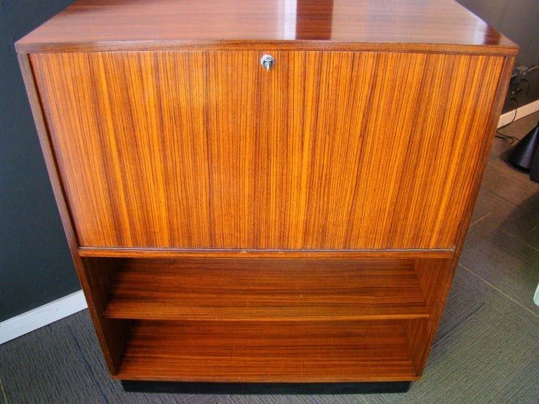 Made in Belgium by Belform, this highly figured, linear-grained Jacaranda rosewood cabinet, designed by Alfred Hendrickx, serves nicely as a secretary or writing desk and could easily be re-configured into a stunning bar cabinet.  It features a