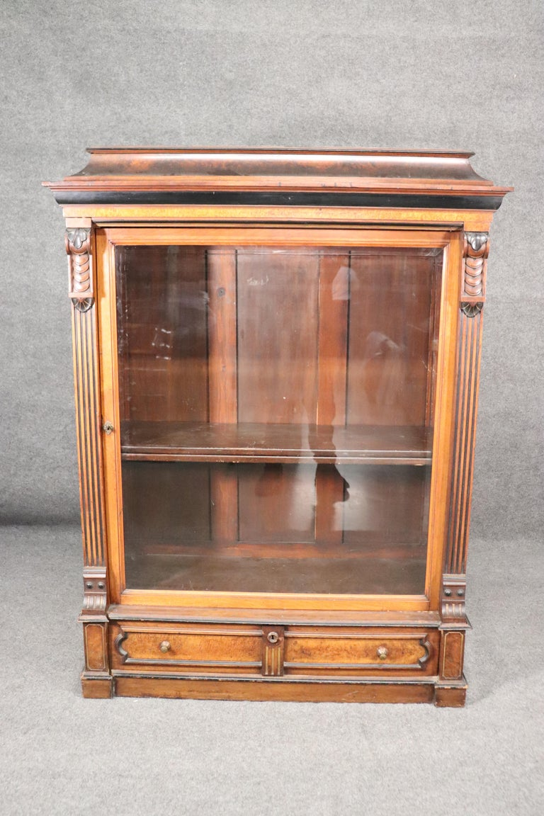 This is a gorgeous bookcase or vitrine measuring 66 inches tall x 51 wide x 19 inches deep. The condition of the piece is very good considering its approximately 150 years old. The cabinet is burled walnut and done in the Renaissance Revival style