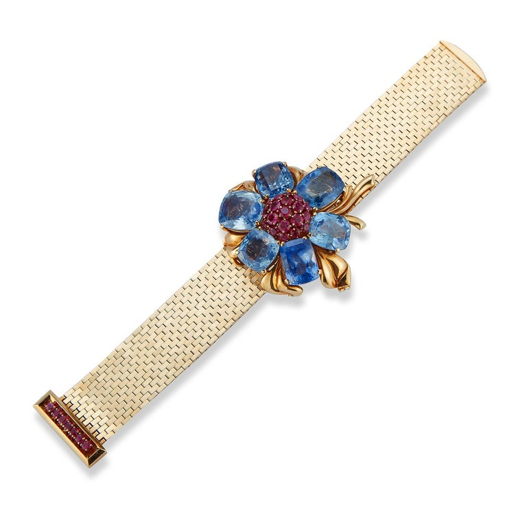 Rare and Iconic Van Cleef & Arpels Passe Partout Sapphire & Ruby Bracelet ,  With a removable  flower brooch. This bracelet can be worn with or without the brooch.  Six cushion cut sapphires surrounding round cut rubies all set in 18k yellow gold