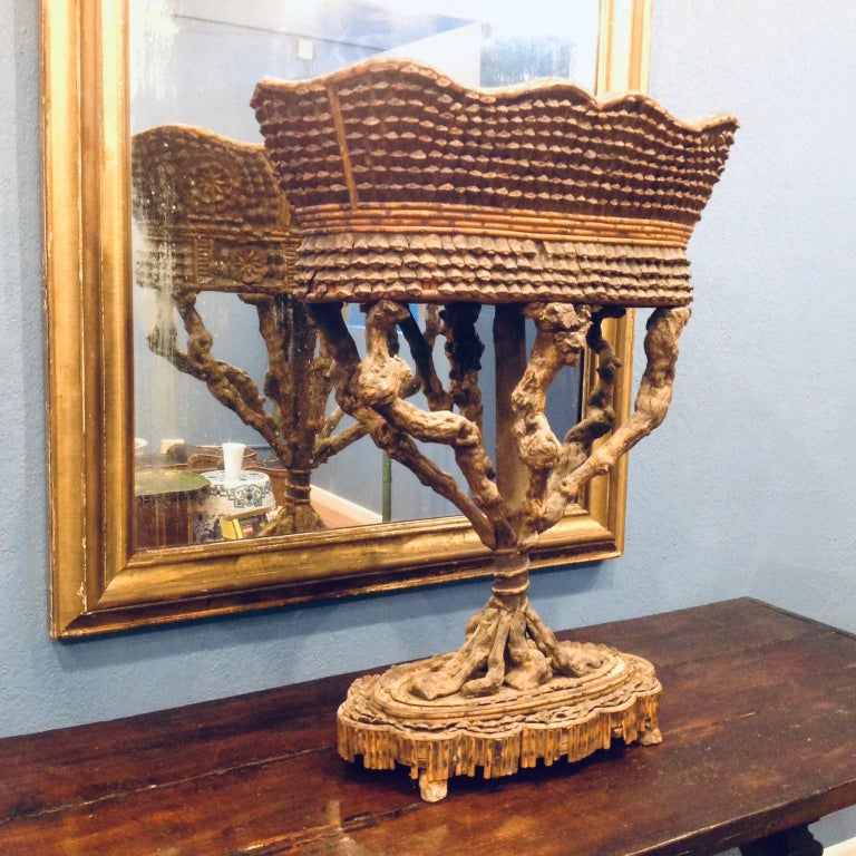The piece is fashioned with a root pedestal and the surround is carved from pine cones.