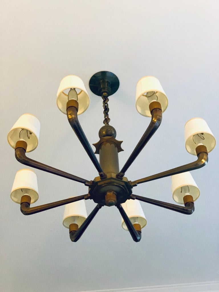 This light came out of a bank in France and is probably early 1920s-1930s. A solid bronze stem leads up to a star and ball detail. This chandelier is solid brass and quite heavy. A very special piece. Looks equally handsome with or without shades.