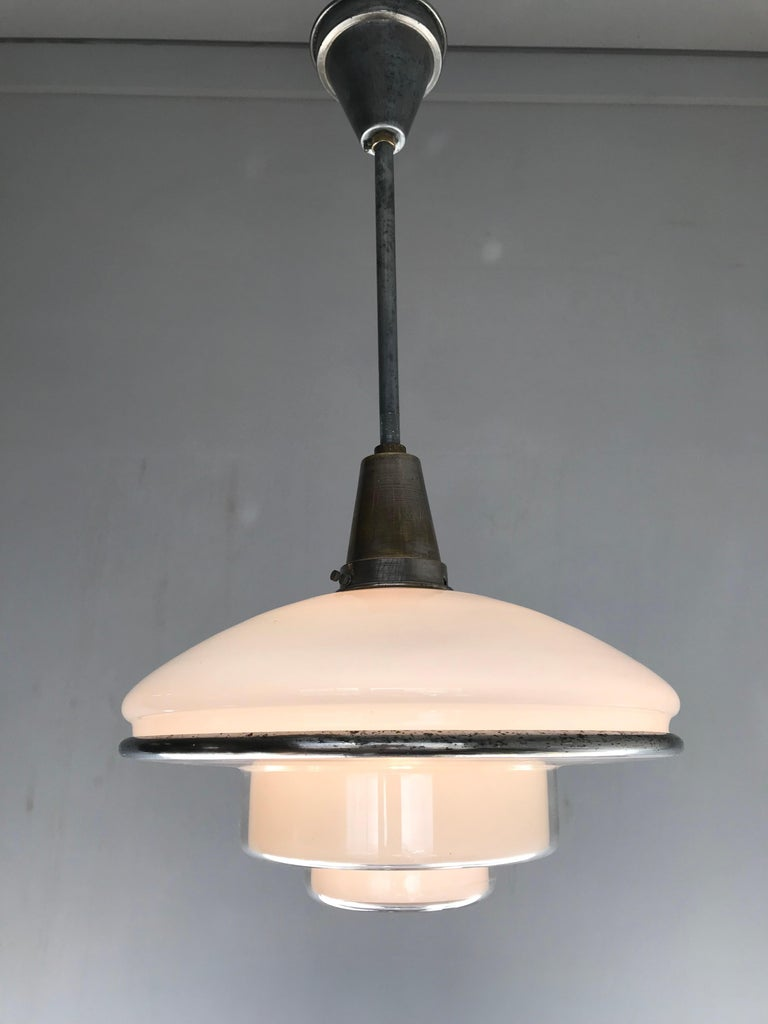 1920s Bauhaus style light fixture with original rod and canopy.  This stunning pendant is in very good to excellent condition and thanks to its shape this timeless piece of lighting art can be used in various kinds of interiors. With a two-piece