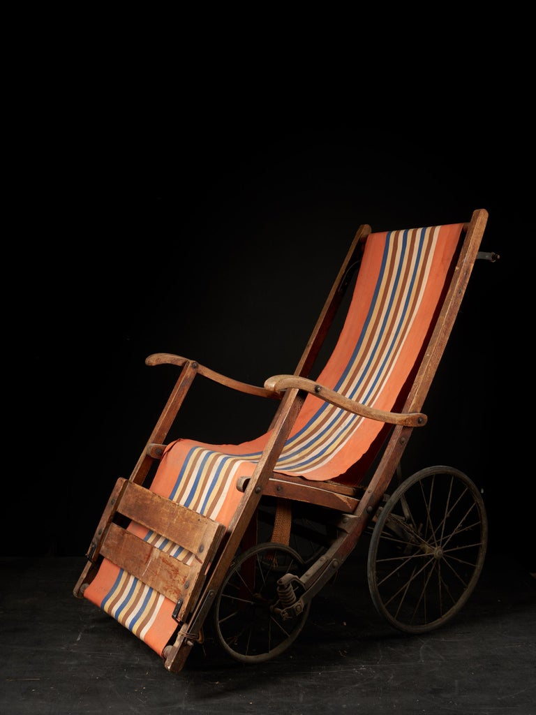 This antique pushchair is fully pliable. it's chair very well constructed with an iron under-brace and solid wood. It features four wheels and a full fabric seat with wooden footrest. The iron wheels are covered in full rubber. The fabric has been
