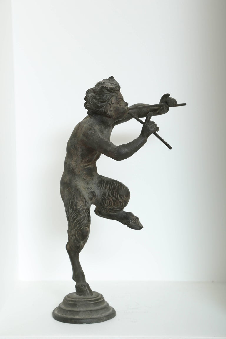 Rare antique bronze statue of Pan the Greek/Roman fertility God of the forest, from the personal collection of Juan March of the Fundación Juan March (Juan March Foundation). The sculpture features Pan half-man, half-goat playing a pair of flutes.