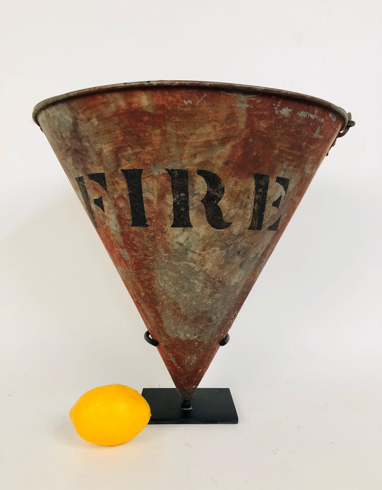 A rare cone shaped galvanized steel circa 1930s antique fire bucket on a custom made steel stand. untouched surface. The handle stays in the upright position or can be put down. Total height with the handle up is 23