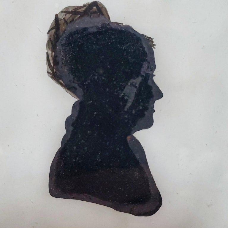Among the rarest American silhouettes are those using the reverse painting on glass technique know by its French name eglomise. This charming profile silhouette depicts an older woman, looking to her right, appearing to be missing her upper teeth