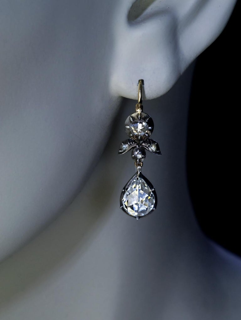 Circa 1800 – 1830  This pair of rare Georgian era dangle earrings is set with sparkling antique rose cut diamonds. The diamonds are set in silver and backed in 14K gold.  The two drop-shaped diamonds measure approximately 9.3 x 7.2 x 2.7 mm and 9.3