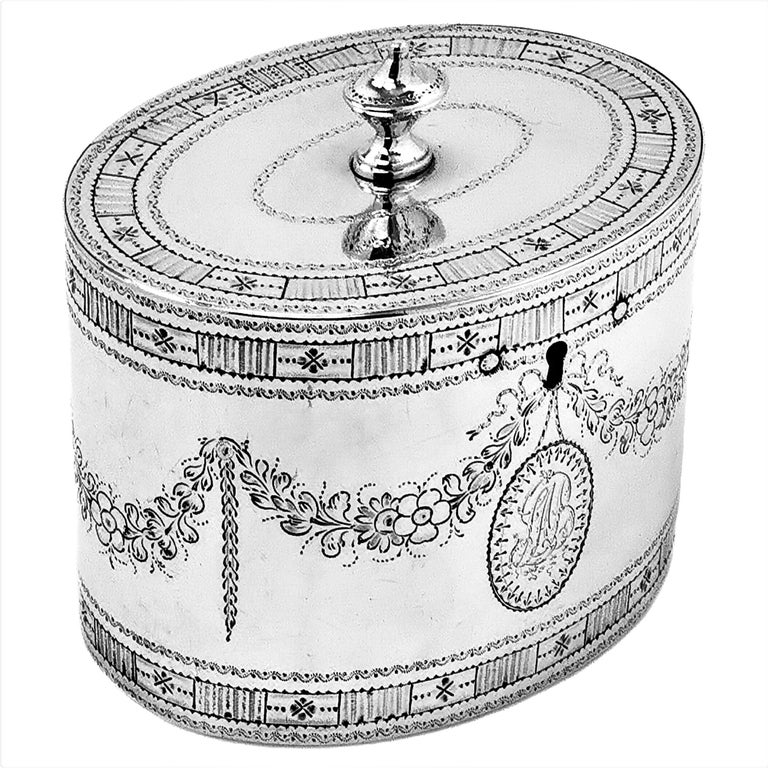 A beautiful Antique George III is a classic oval can shape Tea Caddy and is decorated with an ornate engraved border on both top & bottom rims of the body and around the rims of the lid. The body of the Caddy also includes a floral swag and bow