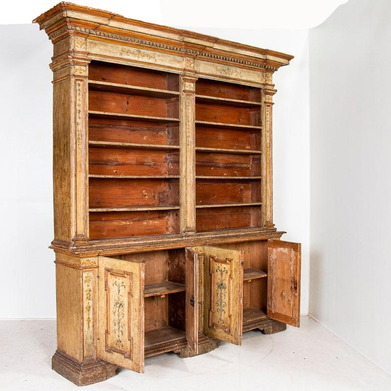 It is rare to find an original painted bookcase of this quality, making this a special find. The original painted finish adds both grace and grandeur to this striking display cabinet from Italy. Muted colors of cream, ocher, blue and green add depth