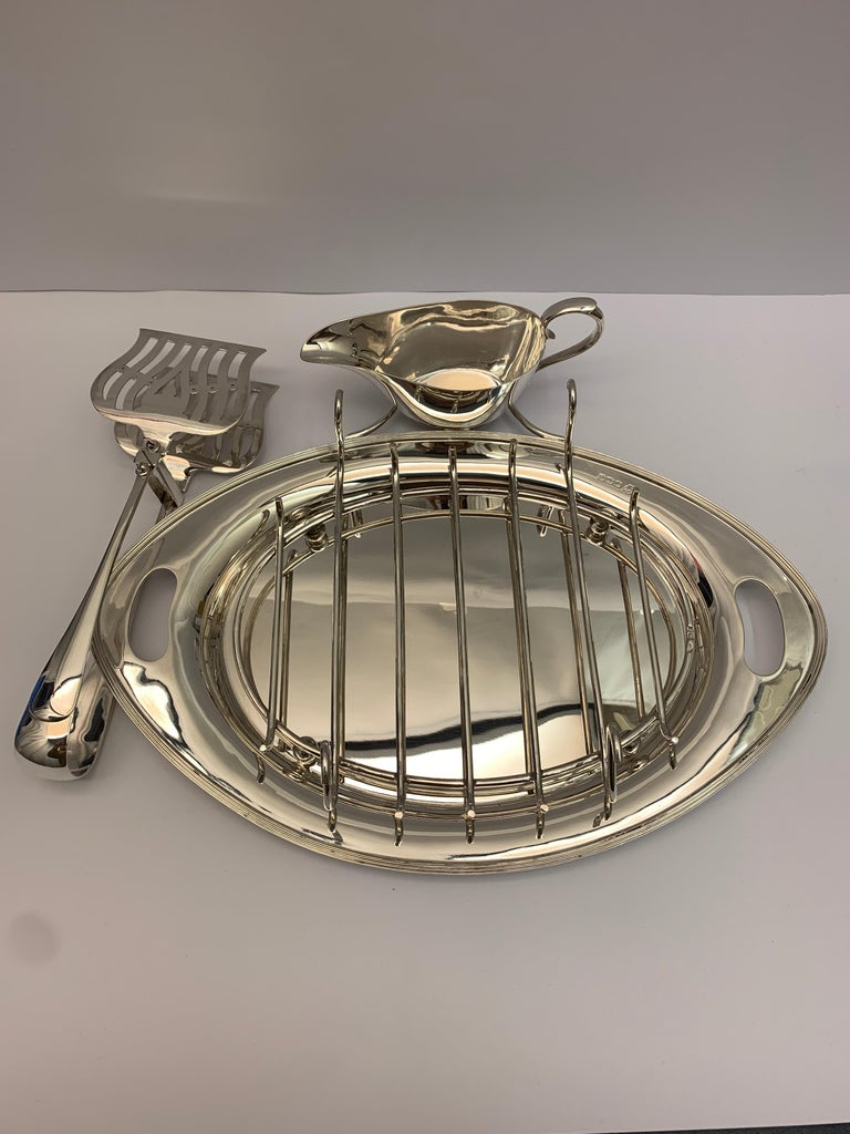 A rare antique silver asparagus serving dish with silver serving tongs, rack and a silver sauce boat.