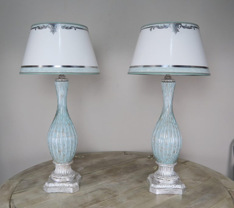 Pair of rare aquamarine colored handblown Italian Murano Lamps on silvered bases. The lamps are crowned with hand painted parchment shades with coordinating aquamarine and silver detailing.