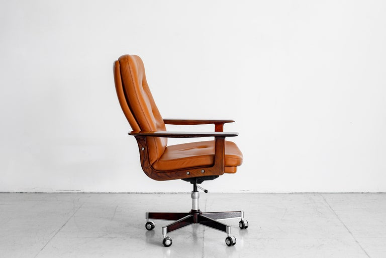 Rare Rosewood and original caramel leather executive office chair by Arne Vodder.  Original rosewood base and arms. Chair swivels and pivots.  Adjustable in height.  Leather has wear typical with its age - see detailed photos.