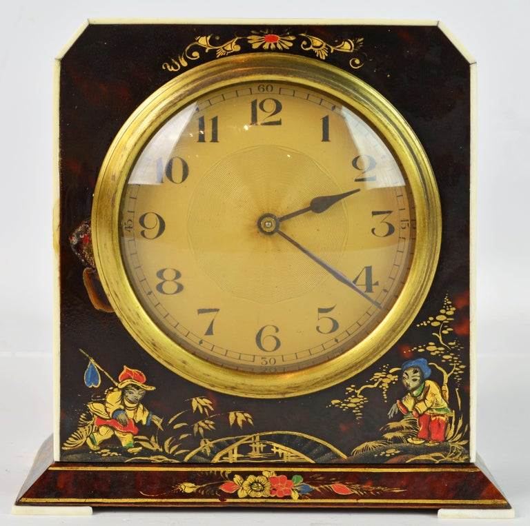 This very stylish clock would have been made in the Art Deco period around 1930. It is made of wood covered with chinoiserie lacquer and gilt decorated tortoise shell with an ivory trim around the front and slices of ivory for feet on each corner of
