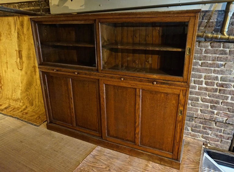 Solid oak Arts & Crafts Barrister's cabinet with sliding glass doors that glide effortlessly and sunken brass handles. Separates at the mid point and features two knobbed pull out leaves for jotting/referencing use. Original old patina betrays the