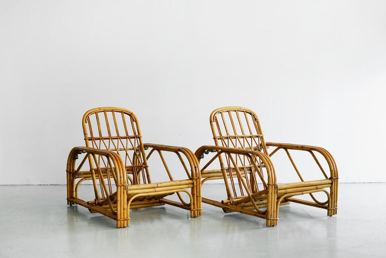 Rare pair of signed Audoux Minet rattan lounge chairs with ability to recline. Original piece of bamboo lays between 3 brass rings that chooses your recline.  Signature of brand on chairs.  Cushions manufactured to customer's specification.