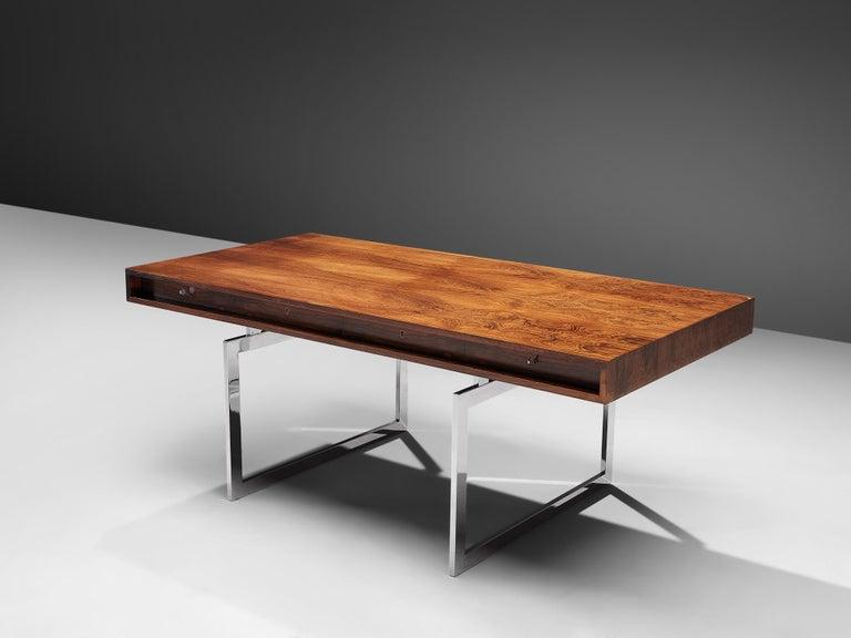 Bodil Kjaer for E. Pedersen & Søn, table model 901, Brasilian hardwood and chrome steel, Denmark, 1959.  This freestanding desk in rosewood is designed by the Danish designer Bodil Kjaer. The desk can be used with multiple purposes, as a writing