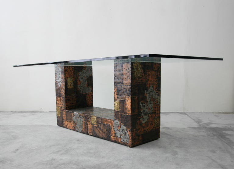 From a one owner estate, comes a rare opportunity to own an authentic and very rare Brutalist metal patchwork pedestal dining table by Paul Evans. Table is comprised of 2 L-shaped pedestals clad, in riveted bronze, copper, brass and pewter pieces in