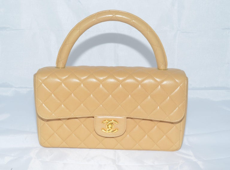 Vintage Chanel bag is featured in a beige-colored quilted leather with a single top handle, back slip pocket, and a signature CC turnlock closure in gold-plated hardware. Interior is fully lined in leather and offers one slip pocket and one zippered