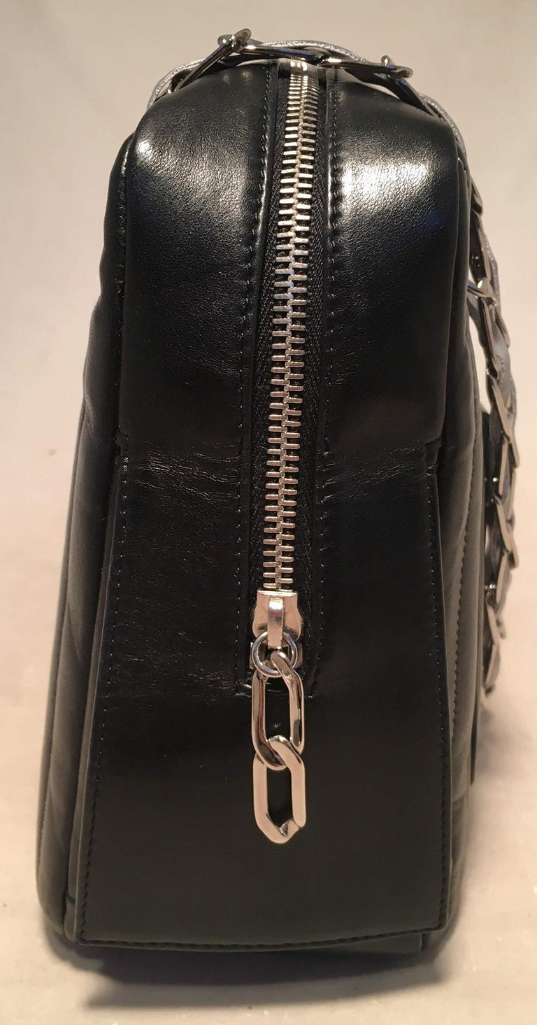 Chanel Mademoiselle Ligne Vertical Quilted Camera Bag in excellent condition. black vertical stripe quilted lambskin exterior trimmed with silver hardware and a unique woven chain and reflective ribbon shoulder strap that can be worn long or short.