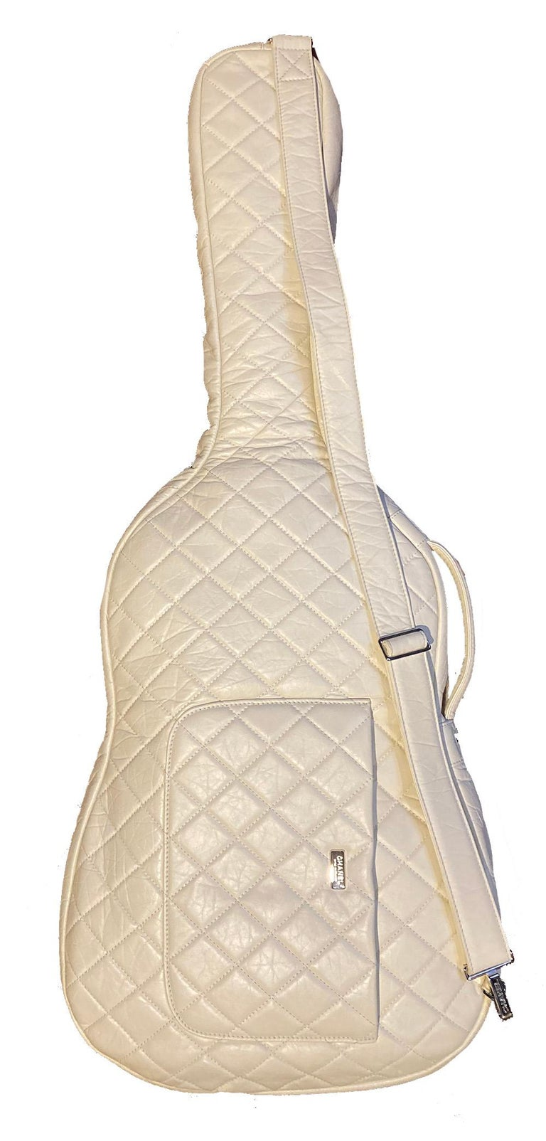 Rare Chanel white leather guitar case. excellent condition from spring 2009 runway show. cream quilted leather exterior with silver hardware and matching adjustable shoulder strap. front zip pouch pocket. Double zip closure opens to cream soft