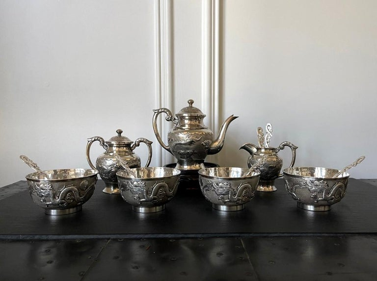 A Chinese export sterling silver tea set comprised of 13 pieces including tea pot, sugar, creamer, four tea bowls and six tea spoons, circa 1910s-1920s. Featuring matching chased relief dragon and cloud motif on a contrasting tightly hammered
