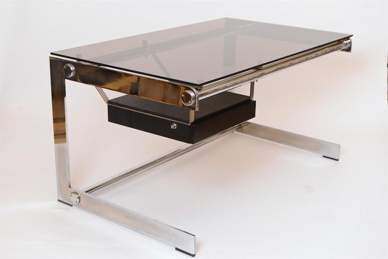 Rare chromed steel and grey glass desk, circa 1965.   Designed by architect Gilles Bouchez and produced by Airbourne in France. This is the smaller version   Sleek, minimal and ahead of its time.   Glass is original and stamped
