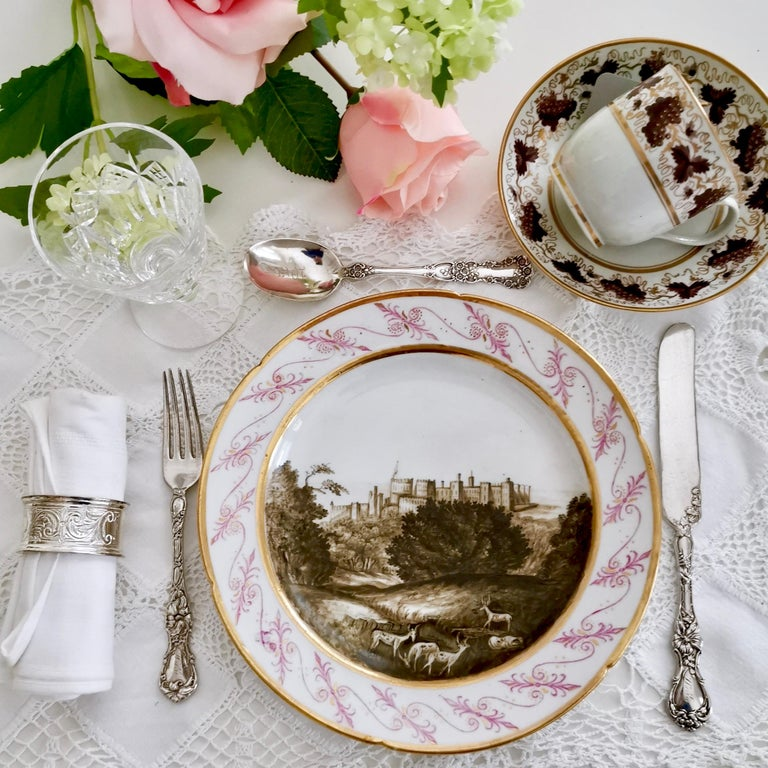 This is a dessert plate made by Coalport in circa 1805, which was the late Georgian era. The plate is decorated with a superbly painted named landscape of Windsor Castle in sepia by the famous porcelain painter Thomas Baxter.  Coalport was one of
