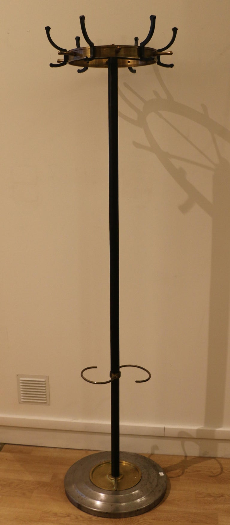 This furniture is typical of Jacques Adnet's work in the early 1950s. This coat stand allows to suspend up to 18 garments. It is also an umbrella stand. The base is made of steel, with two removable brass plaques. The shaft is covered with leather
