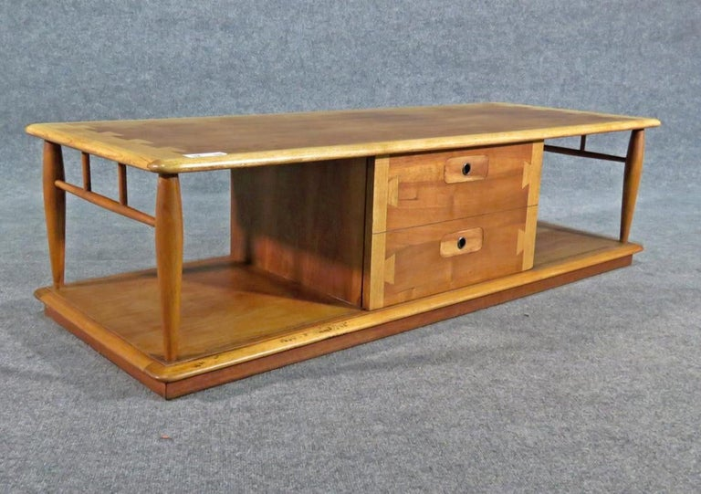 Lane coffee table with dovetailed walnut and oakwood grain. Features sliding door with storage. (Please confirm item location - NY or NJ - with dealer).