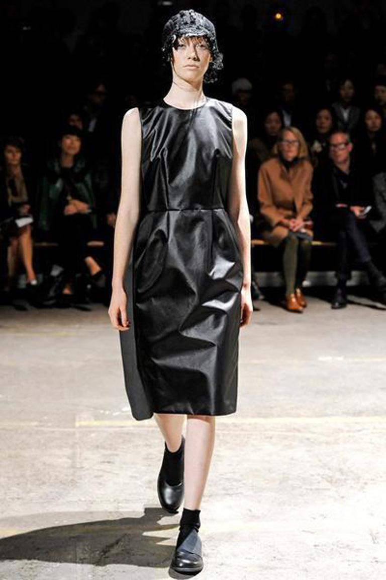 Spring 2011 CDG collection by Rei Kawakubo where she rearranged or appeared to turn clothes upside down. The dress being presented is made in 3 identically styled attached dresses: black shiny poly; navy wool; and a distressed grey nylon denim.