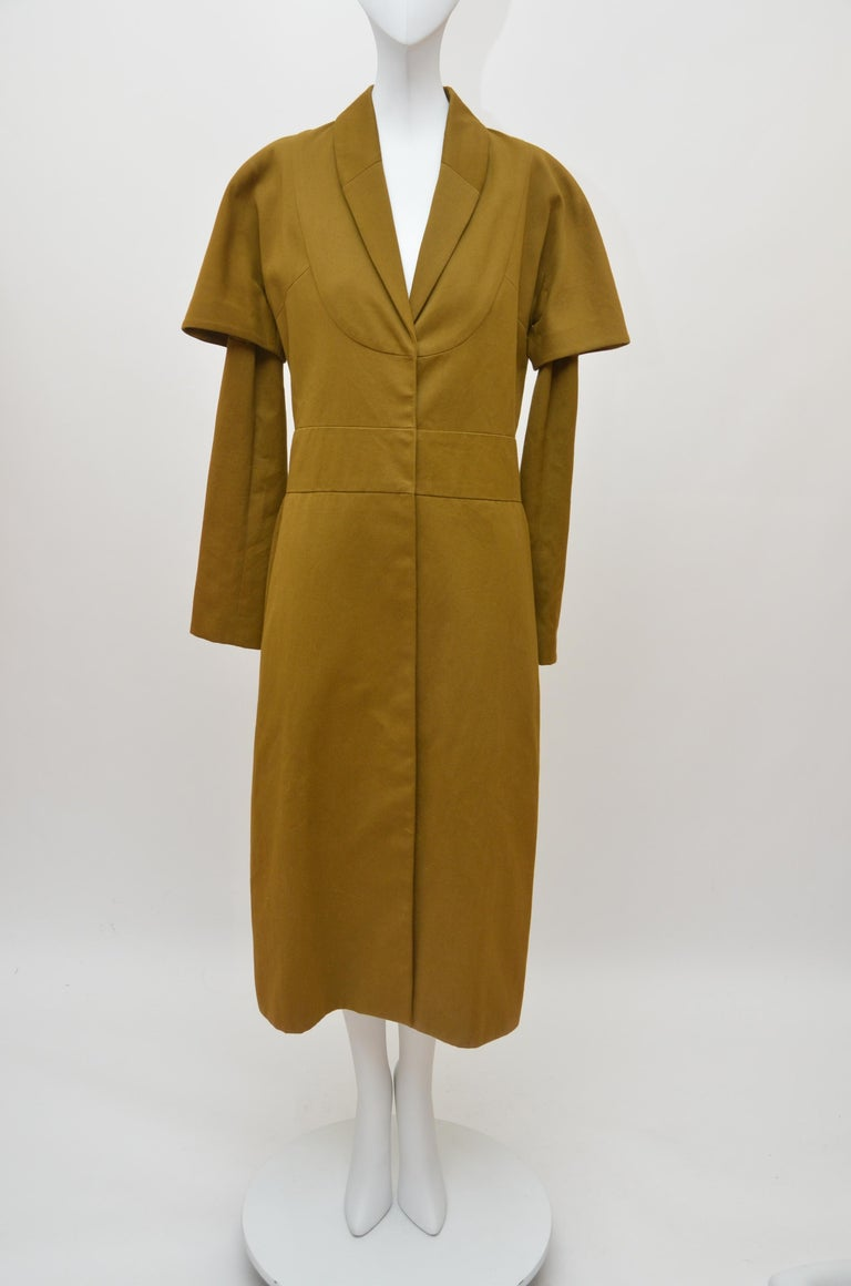 A rare and early Comme des Garçons 'Obi' coat, probably late 1970s, with unusual blue on ivory woven satin label, of heavy cotton, lined in polyester crêpe, with curved front 'bib' panel, under and over sleeves, the waistband applied to the rear