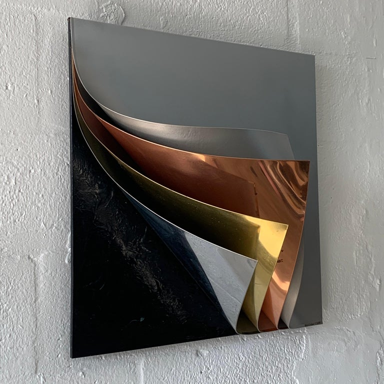Wall sculpture rendered in gray painted metal polished copper brass and chrome with textured black base by Curtis Jere, 1989, signed, C. Jere.