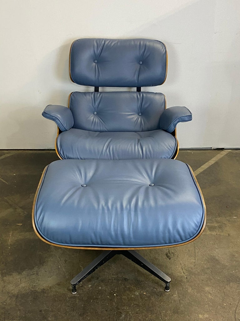 A vintage signed and authentic Herman Miller Eames lounge chair and ottoman in rose wood with new blue leather with smooth and extremely comfortable finish. The wood is cleaned and oiled, no missing parts or damages besides normal wear. The leather