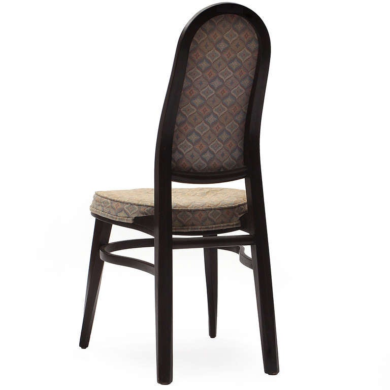 An ebonized mahogany dining chair with twisted front legs, with an upholstered high back rest and oval seat.