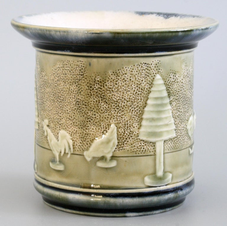 A rare Doulton Lambeth unusual flared rim pot or vase of cylindrical shape decorated in the Toys pattern and dating from 1905. The stoneware pot is molded in relief with a boy doll being chased by a pack of dogs amidst toy trees and with toy hen and
