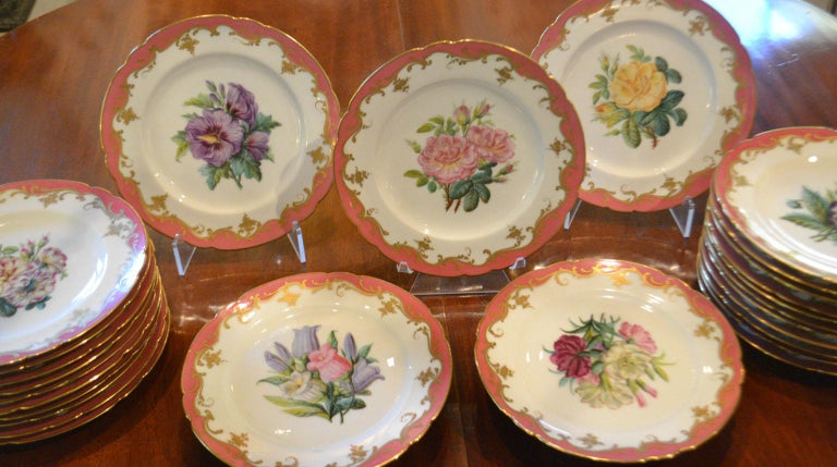 Exquisite collectors item, 24 plates and 2 footed stands, signed Rihouet Paris, circa 1818-1825. Superbly hand-painted pink border with gold edge and gold florals. Service consist of 24 unique botanical 8.25