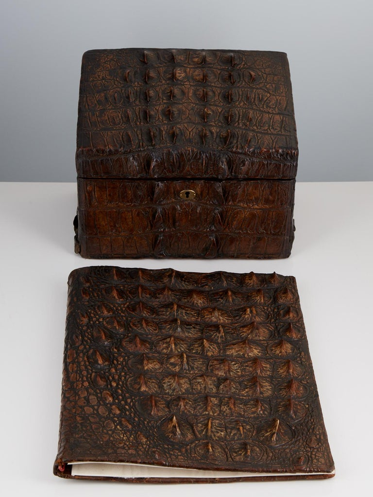 This rugged Nile crocodile set comprises two pieces as shown, one being the stationery box and the desk pad. All the skins on the two pieces are well matched. On lifting the lid of the box it reveals the sections for letters and papers. The desk pad
