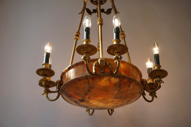 A large and rare early French 20th century Art Deco bronze alabaster eight-light chandelier. Measures:  Height fixture 87 cm. Total height 100 cm. Diameter 65 cm. Twelve bulbs with an E14 fitting.