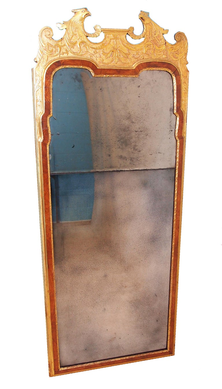 A very rare early 18th century George I period walnut and giltwood pier mirror having eagle heads and scrolls to top and strapwork decoration above split bevelled mirror plates (top original, bottom replaced) bordered by attractive walnut
