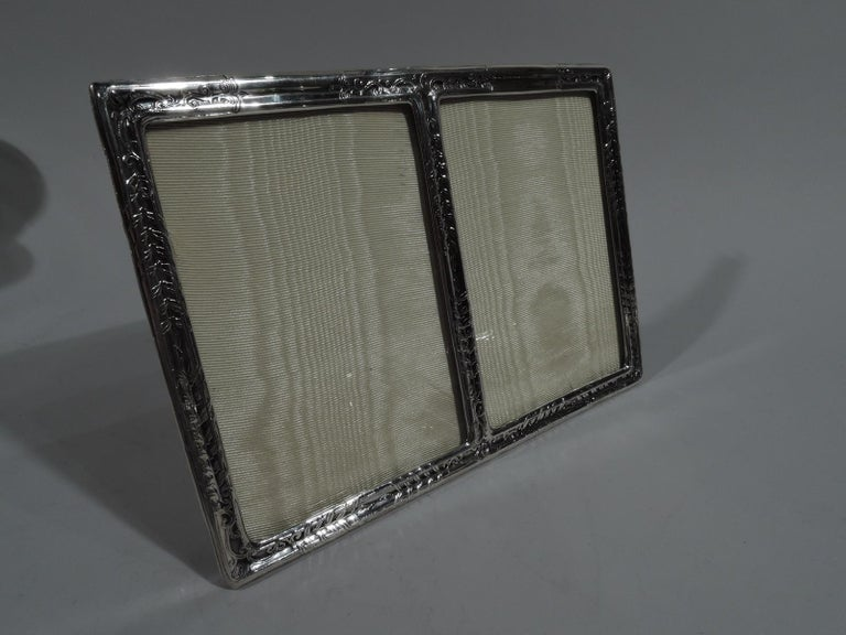 Rare and elegant Edwardian sterling silver picture frame. Made by Tiffany & Co. in New York. Two vertical rectangular windows in rectangular surround acid-etched with stylized leaf bands and scrollwork. With glass, silk lining, and silver hinged
