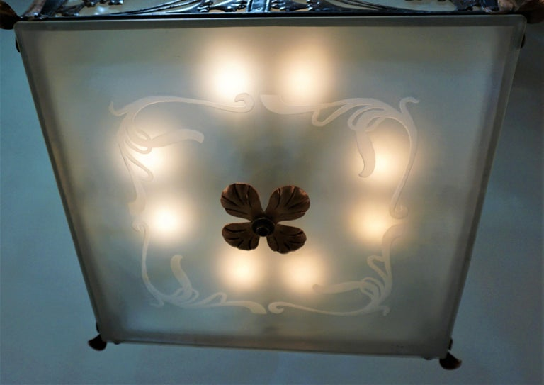 A rare English Arts & Crafts, Art Nouveau cutout copper panels, bronze and etched glass chandelier. New wiring with eight lights, 60 watts each Measurement: 20