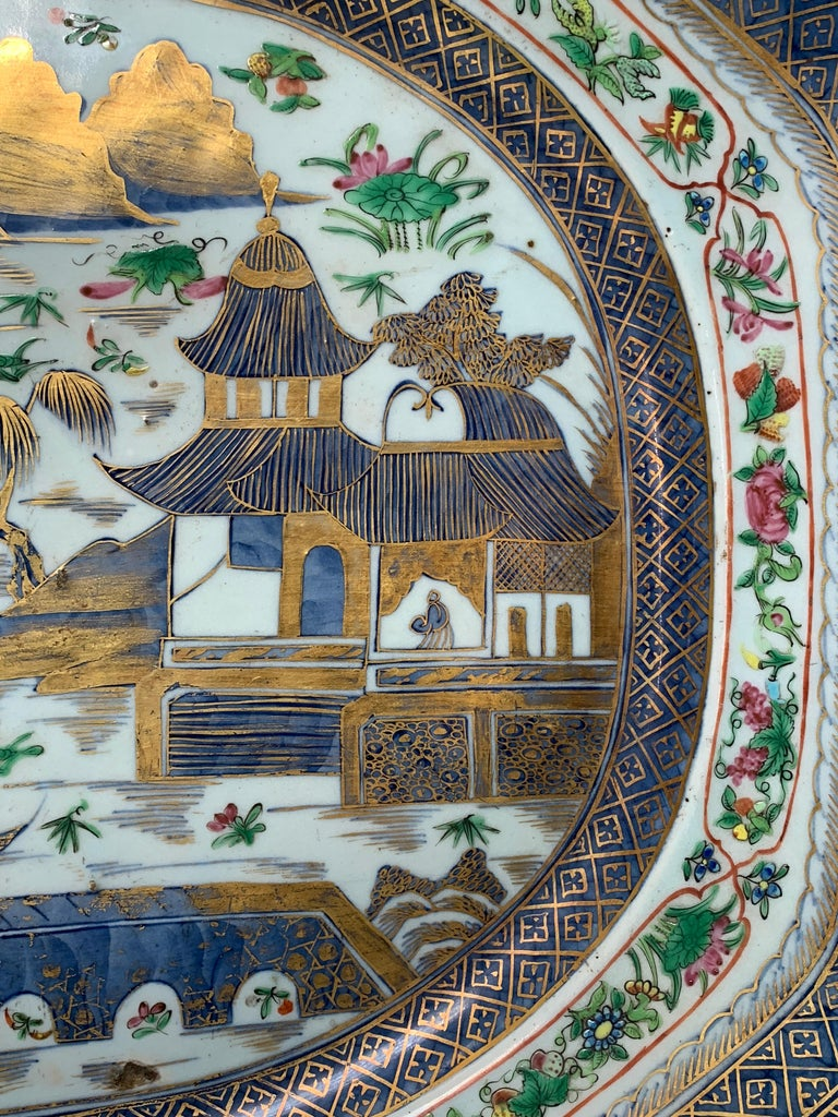 A stunning very large platter with underglaze blue and then with additional famille rose or rose medallion frieze added over the glaze and then further embellished with minutely painted highlighting in gold.